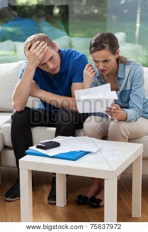 Poor Couple Reading Unpaid Bills