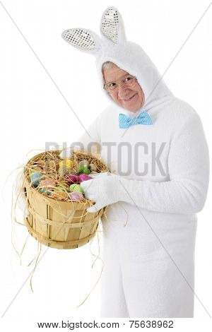 A senior adult man in a white bunny suit happily holding a bushel basket full of colorful eggs.  On a white background.
