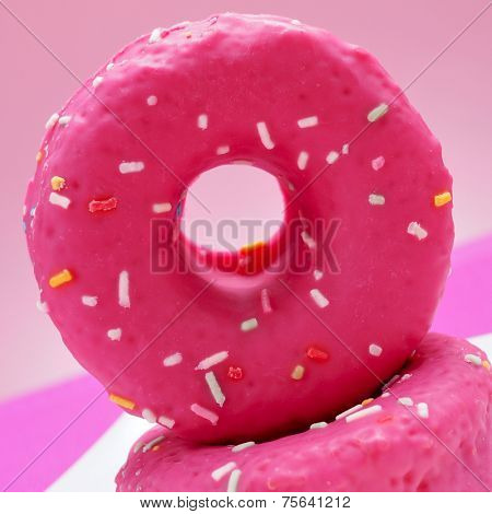 closeup of some appetizing donuts coated with a pink frosting and sprinkles of different colors