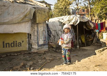KATHMANDU, NEPAL - DEC 16, 2013: Unidentified poor child near their houses at slums in Tripureshwor district. Caste of untouchables in Nepal, is about 7 % of population.