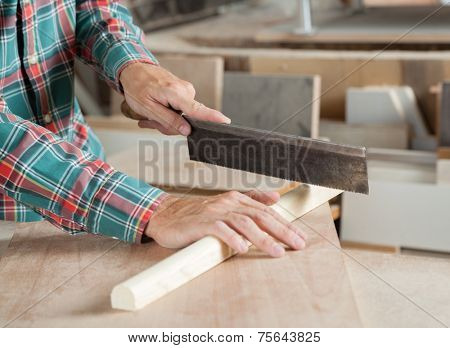 Carpenter's hand using small saw to cut wood in workshop
