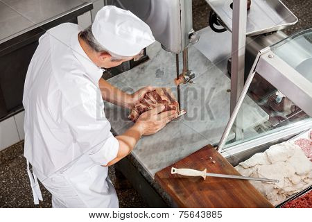 High angle view of butcher cutting meat with bandsaw in butchery