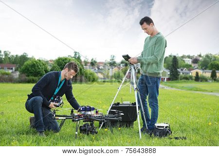 Young technicians working on UAV spy drone in park