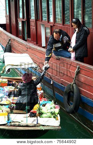 Vietnamese woman selling goods and snack on her boat near tourist argosy.