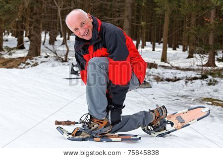 elderly man in winter snowshoeing