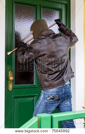 a burglar trying to break a door.