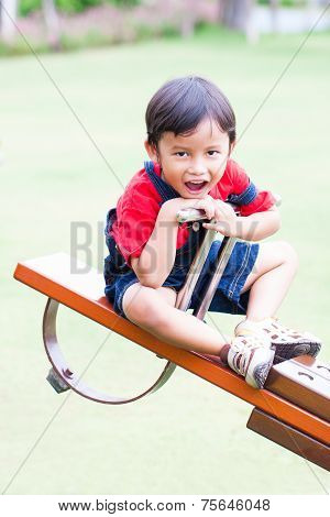 Boy smiling and play at the see-saw