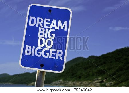 Dream Big Do Bigger sign with a beach on background