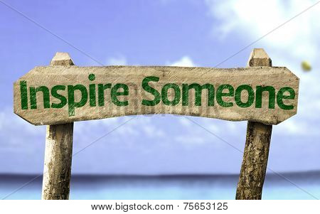 Inspire Someone sign with a beach on background
