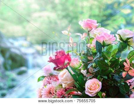 Artificial Roses Flowers Bouquet Arrangement Against Green Blur Background