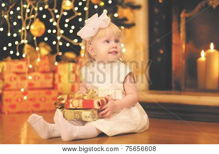 Christmas, Magic, People Concept - Happy Baby With Gift Near Christmas Tree And Fireplace