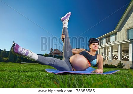 Beautiful pregnant woman doing sport near her house