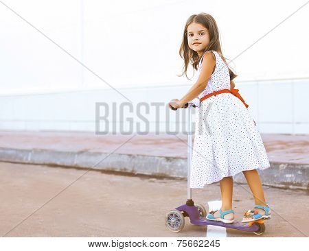 Fun Little Girl In Dress On The Scooter In The City