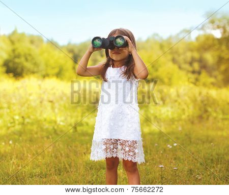 Little Child Looks In Binoculars Outdoors In Sunny Summer Day