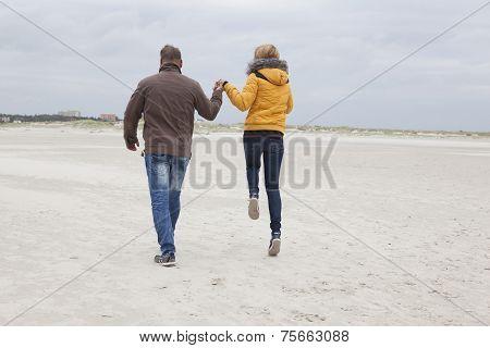Couple On The Sandy Beach In Autumn