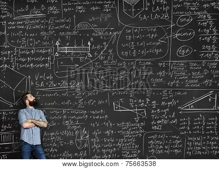 Tattooed Man Looking At Chalkboard With Formulas