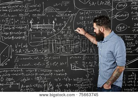 Bearded Hipster Writes Formulas On A Chalkboard