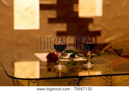 restaurant table red rose and glass of wine with low natural candle light