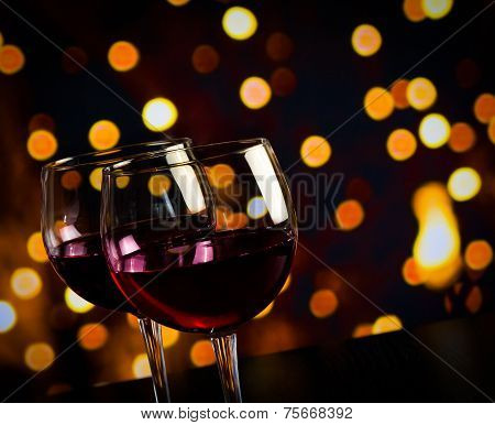 Two Red Wine Glasses On Wood Table Against Bokeh Lights Background