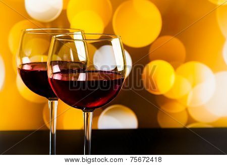 Two Red Wine Glasses On Wood Table Against Golden Bokeh Lights Background