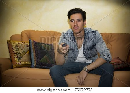 Unhappy, Bored, Unsure Young Man With Remote Control Watching Tv