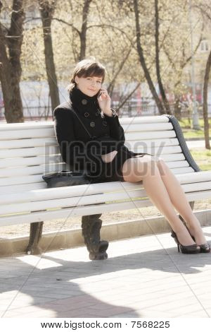 Pretty Woman On Bench With Cellphone