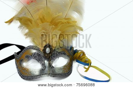 Silver carnival venetian mask with feathers and colorful serpentine.