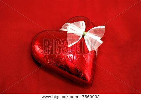 Chocolate heart on red background