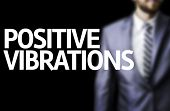 image of vibrator  - Positive Vibrations written on a board with a business man on background - JPG