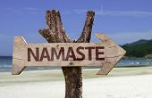 stock photo of namaste  - Namaste wooden sign with a beach on background - JPG