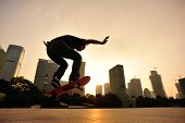 picture of skateboarding  - young woman skateboarder skateboarding at sunrise city - JPG