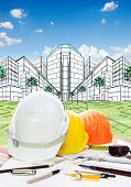 image of land development  - architect working table with writiing tool safety helmet and perspective plan drawing of new building construction project for land development and real estate design - JPG