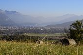 stock photo of annecy  - Landscape of Annecy lake city and mountains from fields with haystack in France - JPG