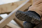 stock photo of rafters  - Roofer Sitting On Rafters Of Newly Made Roof - JPG