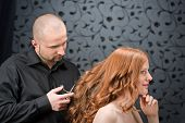 stock photo of hair cutting  - Professional hairdresser with long red curly hair fashion model at black luxury salon hair cut with scissors - JPG