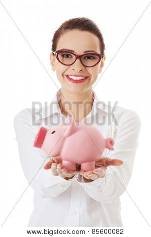 Woman in eyewear holding a piggybank.