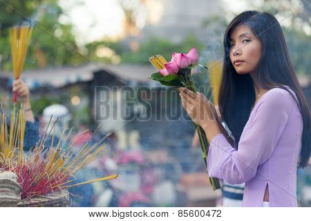 Vietnamese woman praying at temple, holding incense sticks and lotus flowers