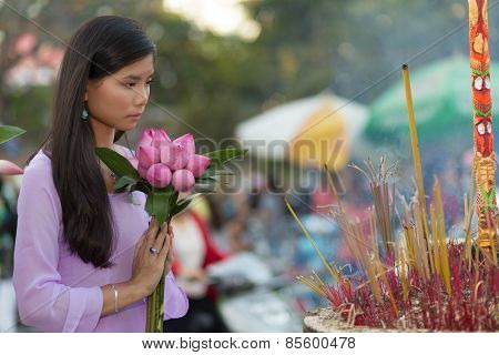 Pretty Vietnamese girl praying as she makes an offering of fresh flowers at a Buddhist shrine during an open air ceremony