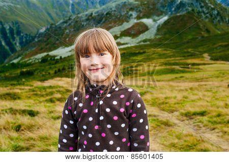 Close up portrait of a cute little girl hiking in mountains, wearing warm fleece jacket