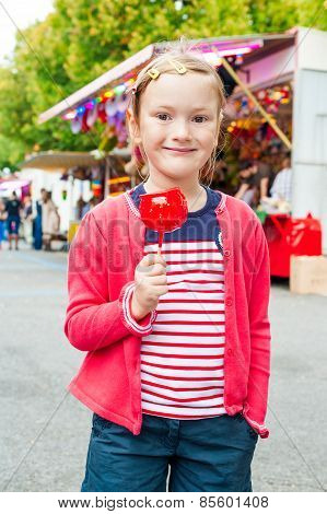 Adorable little girl with candy apple at the fair