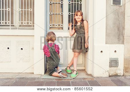 Cute kids playing outdoors; wearing khaki color clothes