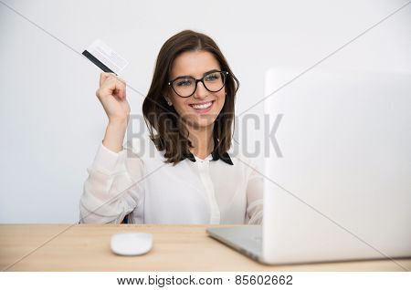 Happy businesswoman sitting at the table with laptop and holding bank card