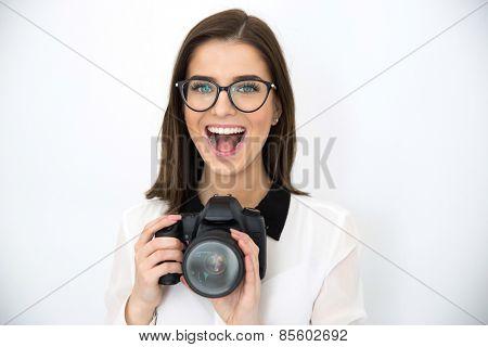 Amazed young beautiful woman holding camera