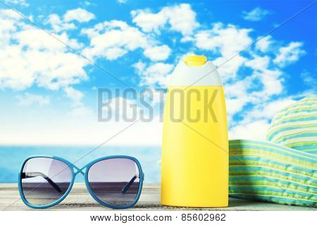 Bottle of suntan cream with sunglasses and hat on table isolated on white