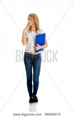Surprised woman looking right, holding binder.