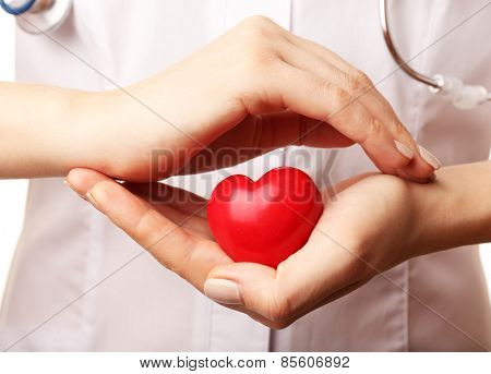 Doctor hands with heart and stethoscope on white background. closeup