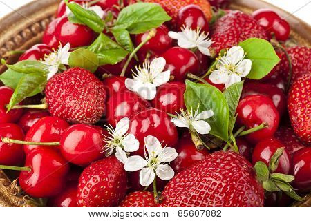 Sweet cherries and strawberries flowering collection surface top view close up