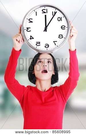 Shocked woman holding office clock.
