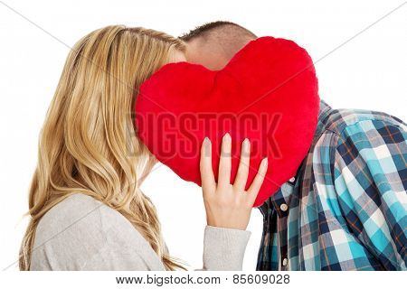 Young beautiful couple whispering behind the pillow