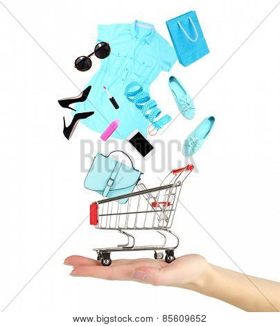 Goods falling into cart isolated on white